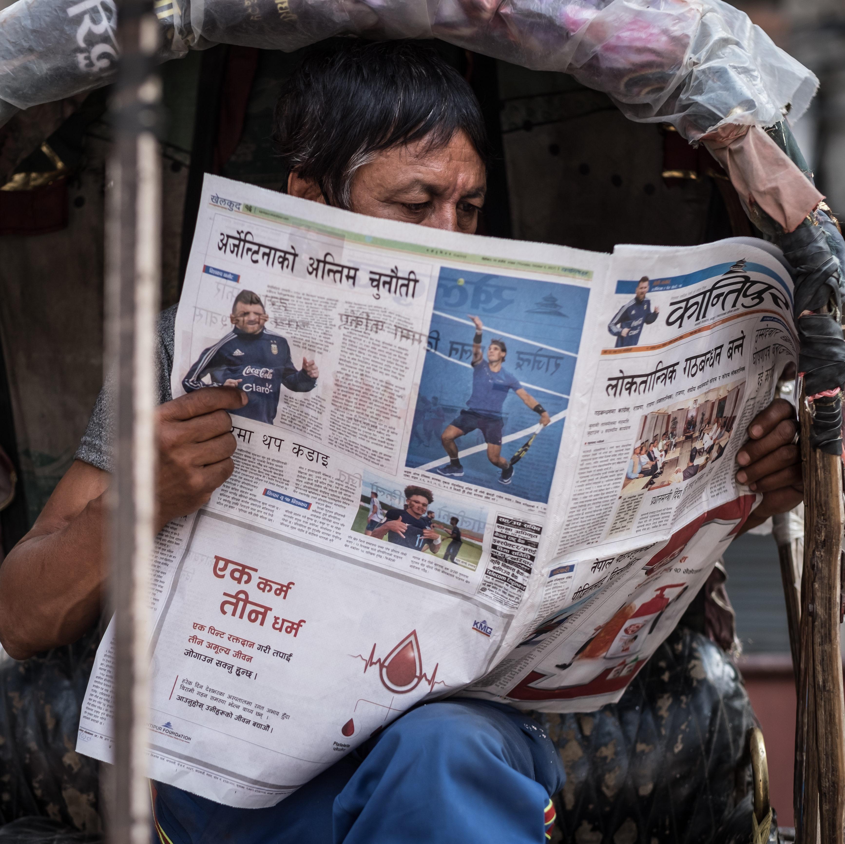 Mies lukee lehteä