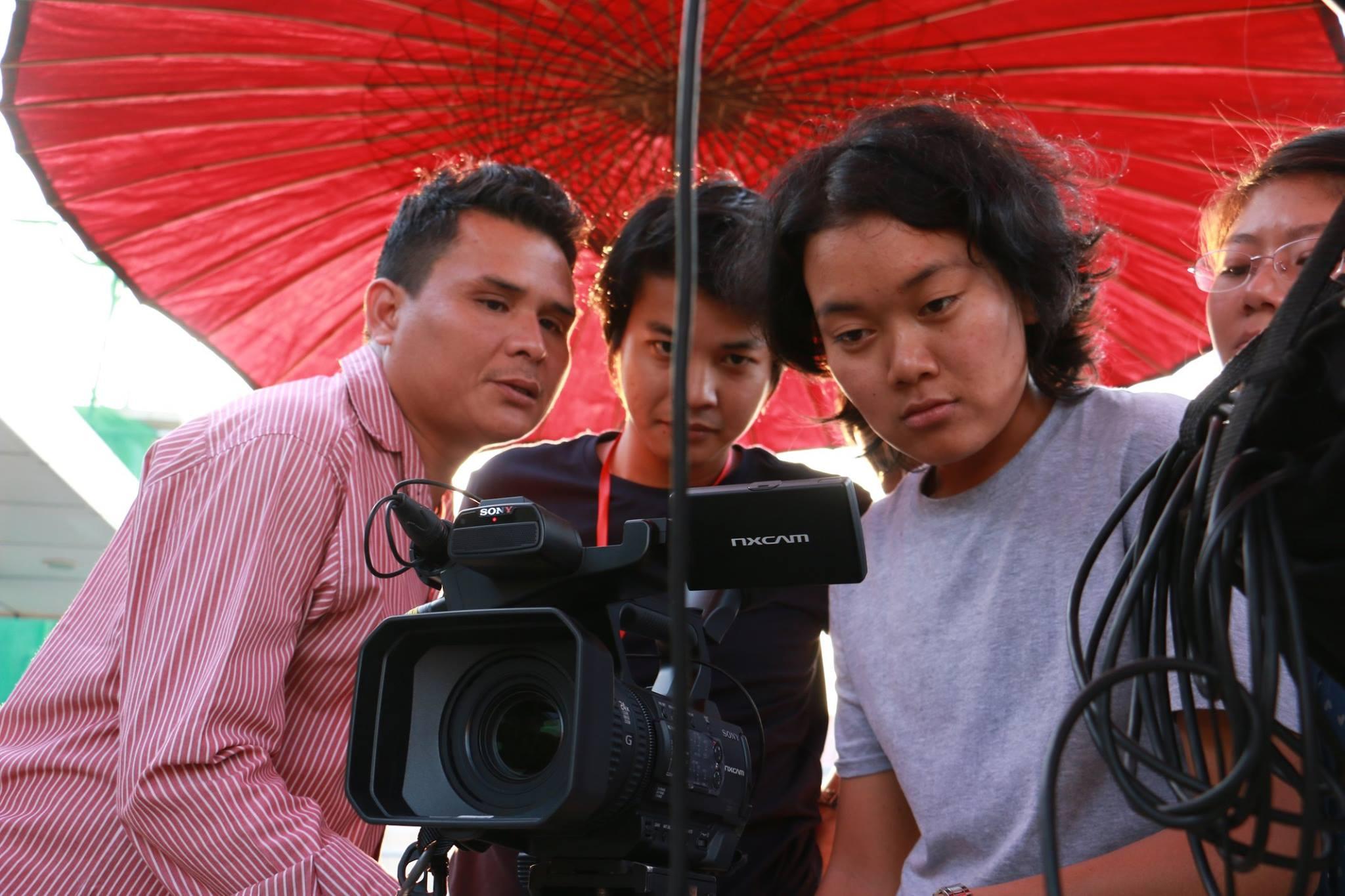 Opiskelijoita Myanmarissa kameran kanssa