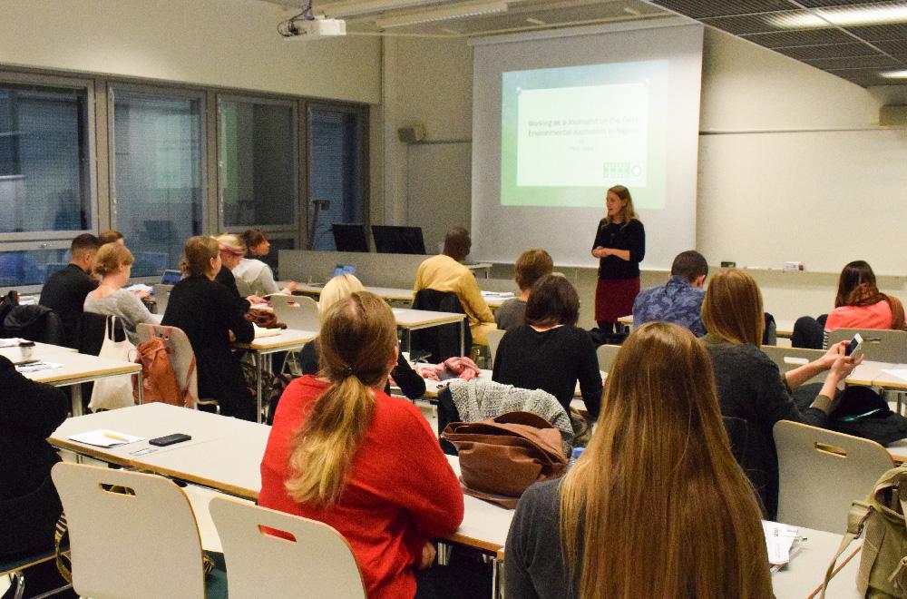 Joukko nuoria opiskelijoita katsoo kouluttajaa luokkahuoneessa.