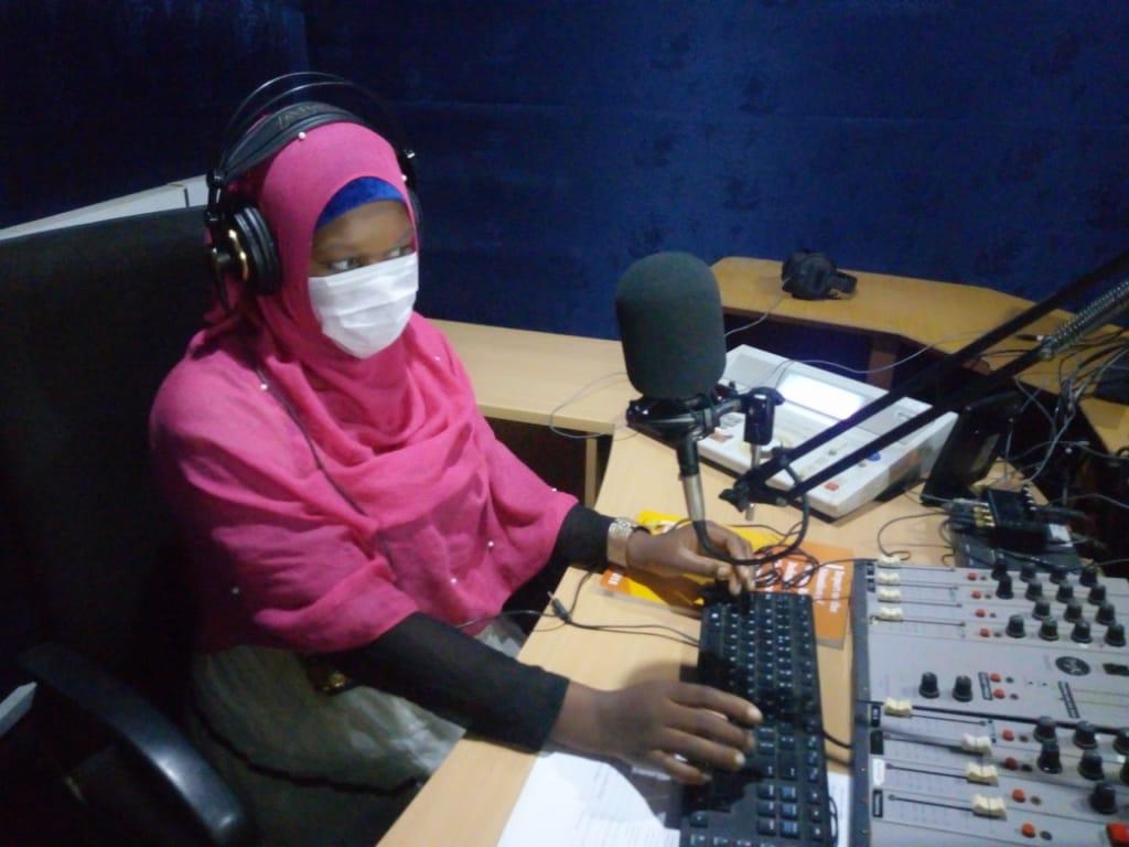 Nainen kasvomaski päällään radiostudiossa