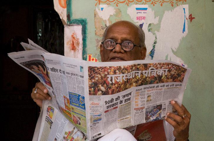 Intialainen mies lukee sanomalehteä