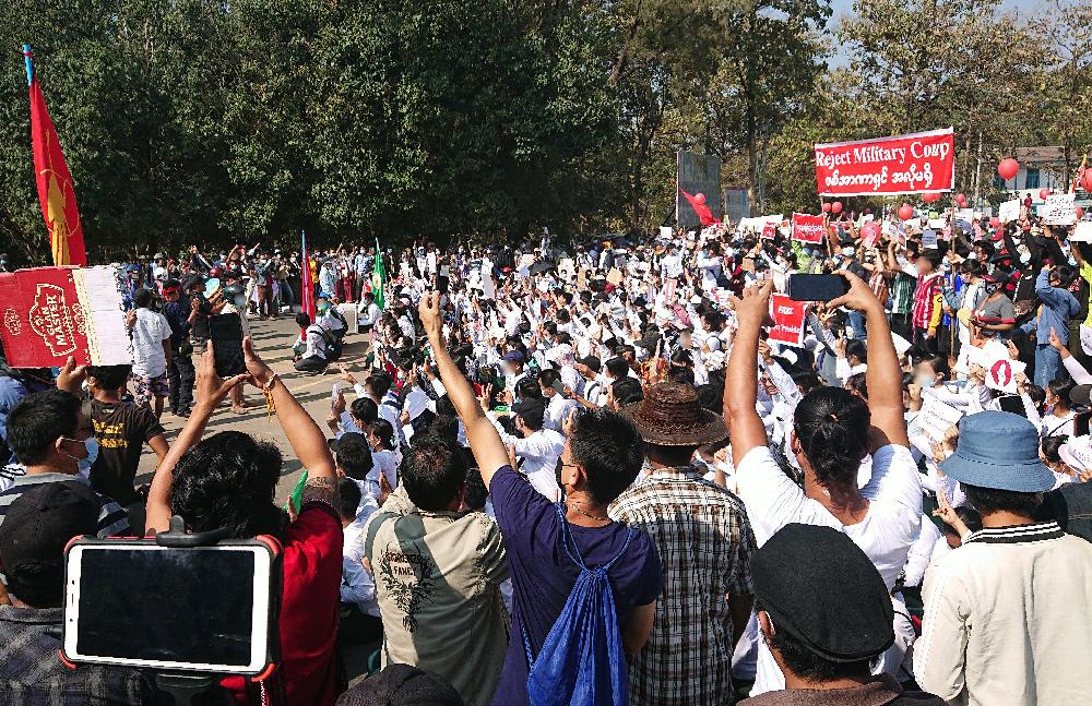 Väkijoukko osoittaa mieltä kadulla, useat kuvaavat kännykällä