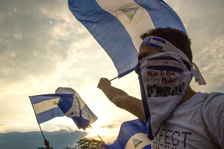 Mielenosoittajat heiluttavat Nicaraguan lippuja, taustalla laskee aurinko