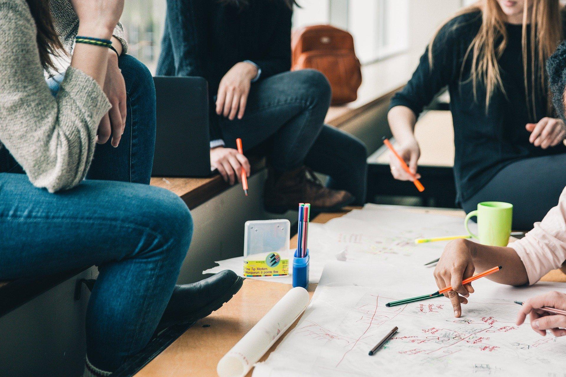Nuoria pöydän ääressä tekemässä ryhmätyötä kynien ja paperin kanssa.