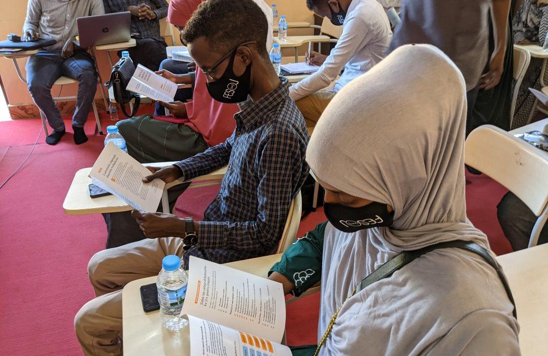Kaksi journalistia lukee opaskirjaa kasvoillaan Fesoj-liiton kasvomaskit
