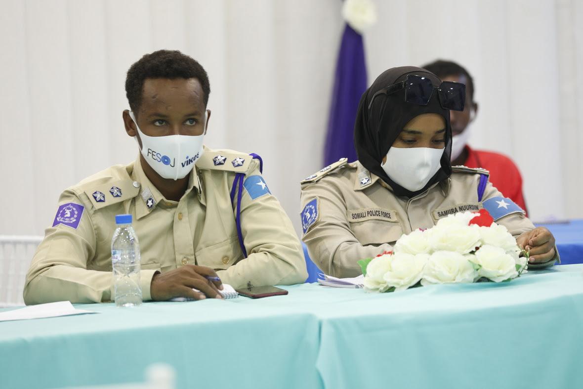 Kaksi poliisia istuu pöydän ääressä kasvoillaan maskit, joissa Vikesin ja Somalian journalistiliiton logot